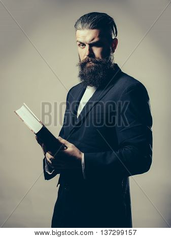Handsome young man with long beard and moustache in black jacket holding open book in studio on grey background