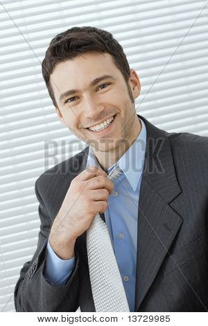 Portrait of happy young businessman at office wearing grey suit and blue shirt, adjusting his tie, smiling.?