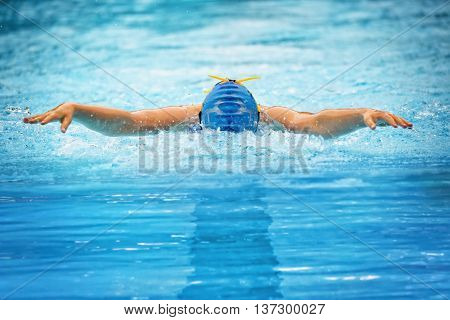 Front view of a female butterfly swimmer who plows powerful through the water.