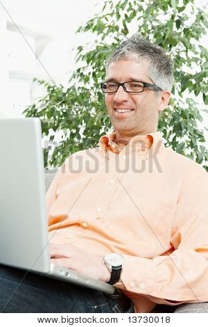 Happy man wearing orange shirt sitting on couch, browsing internet on laptop computer, smiling.?