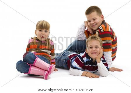 Group of 3 happy children lying on floor wearing colorful, trendy clothes, smiling. Isolated on white background.?