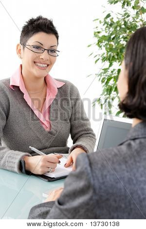 Young businesswomen having a business meeting, writing in personal organizer, smiling.?