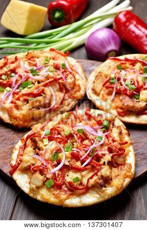 Pizza with chicken meat and vegetables on wooden table