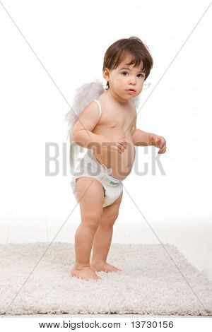 Surprised looking baby girl wearing white angel wings and diaper. Isolated on white background.?