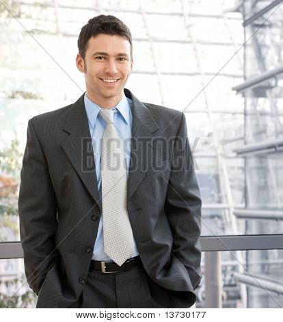 Portrait of happy young businessman standing on office corridor looking at camera, smiling.?