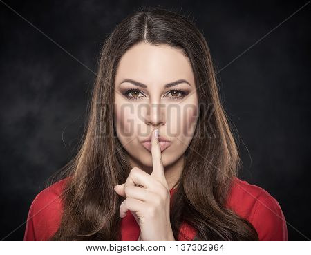 Woman showing silence sign the finger near lips on dark background.