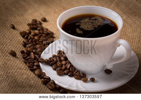 White cup of coffee with saucer and coffeebeans on linen material closeup.