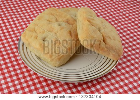 Ciabatta bread on plate on red and white tablecloth