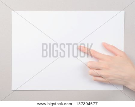 Woman`s finger pointing at the blank paper sheet. On gray cardboard background
