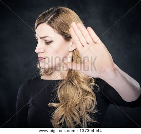 Woman shows stop sign on dark background.