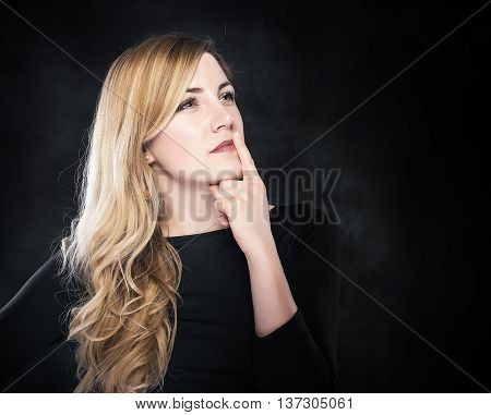 Thinking blond woman on a dark background. Free space for your text or image.