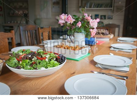 Dinner table set with salad and food ready to be served and eaten.