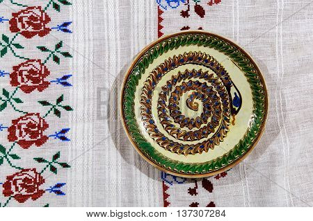 Hand embroidered tablecloth with decorative ceramic plate.Decorative ceramic plate