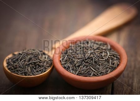 Caraway seeds in a wooden spoon and bowl
