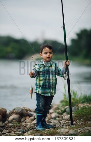 little happy boy fishing on the coast of river