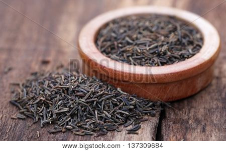 Caraway seeds in a bowl on wooden surface