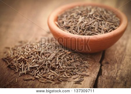 Caraway seeds in a pottery on wooden surface