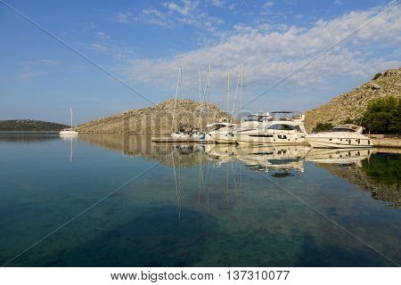 Luxury Yachts mored in colored sunset in a small bay in national park Kornati. Croatia