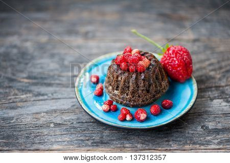 Mini chocolate bundt cake with red berries on a blue plate