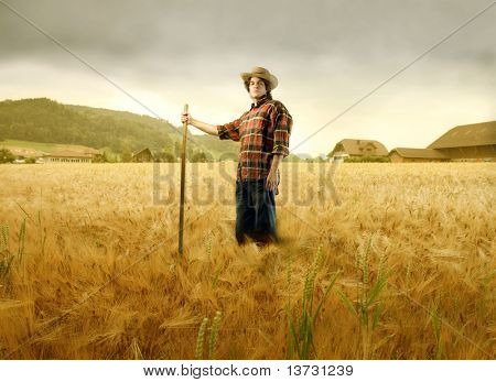 Young farmer standing on a wheat field