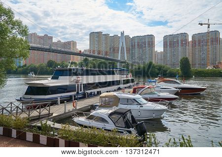 View on Spasskiy bridge and motorboats on Moskva river near Myakinino metro station and Crocus Expo in summer