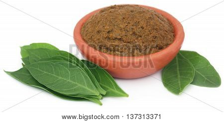 Ayurvedic henna leaves with paste in a bowl over white background