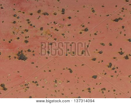 A rusty metal surface showing pits and red discoloration.