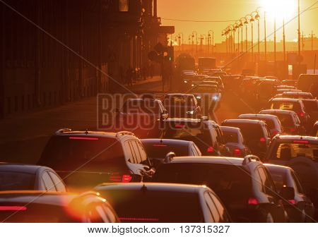 Cars are in a traffic jam during a beautiful golden sunset in a big city.
