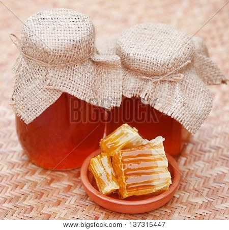 Honey in glass jar with bee hive on textured surface