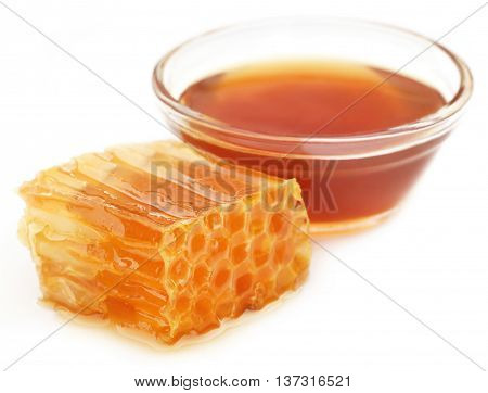 Honey comb with honey in a glass bowl over white background