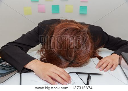 Stressed businesswoman bend down the head at her desk overwork concept.