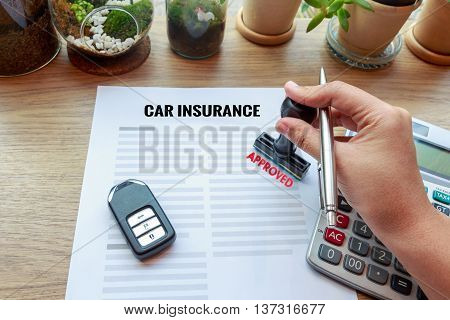Hand holding rubber stamp with approved car insurance car key and calculator concept