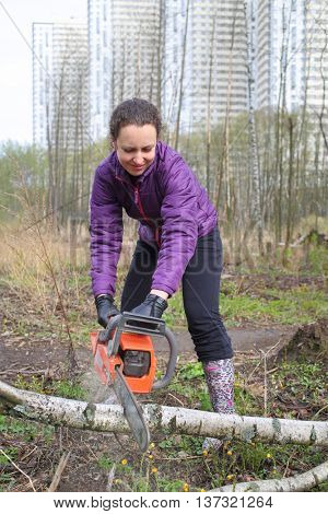 Woman with a chainsaw sawing the trunk of dry wood in the forest