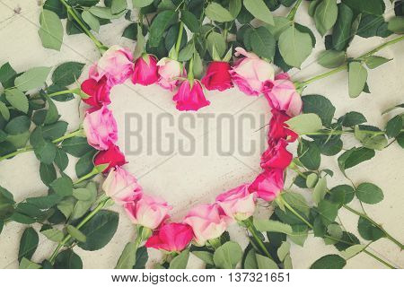 Pink and magenta fresh roses frame in heart shape on white wooden aged background, retro toned