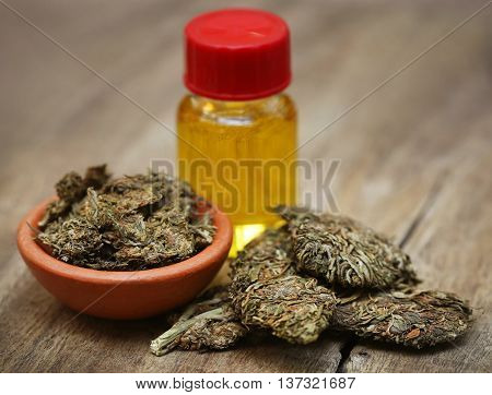 Medicinal cannabis with extract oil in a bottle on wooden surface