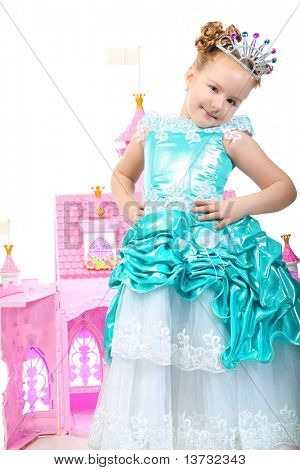 Beautiful little girl in princess dress playing with her toy castle. Isolated over white background.