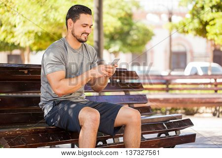 Male Runner Using A Smartphone At The Park
