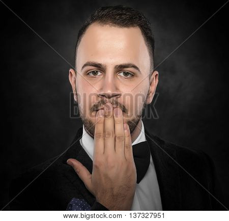 Funny man in suit hand covering mouth over dark background.