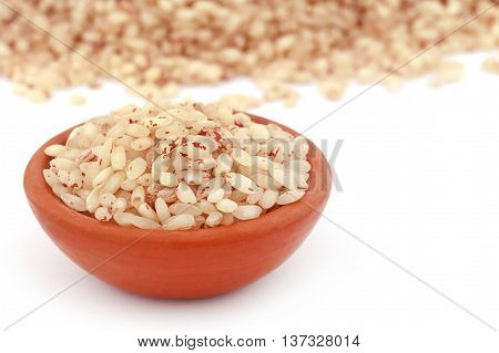 Brown rice in a pottery over white