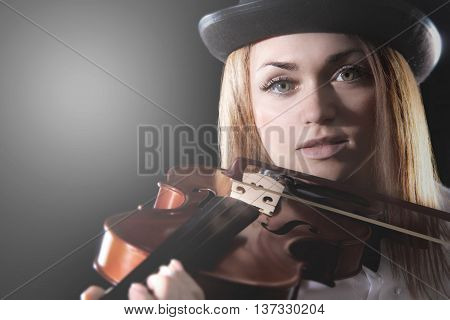 Pretty young woman playing the violin over black background