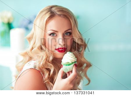 Beautiful blonde girl 20-24 year old holding cupcake in room closeup. Unhealthy lifestyle.