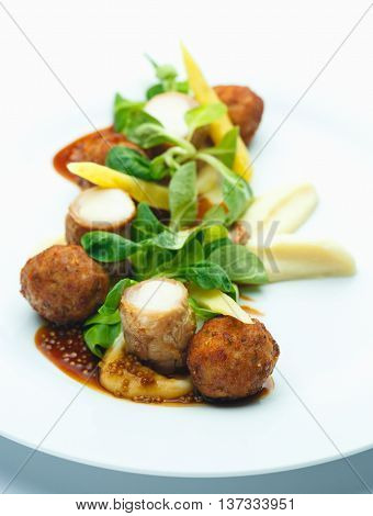 Meatballs with pasta and basil on white plate
