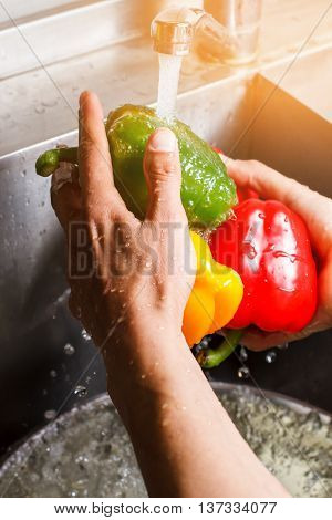 Male hands wash green paprika. Water flowing onto paprika. Green light to your health. Fresh and natural.