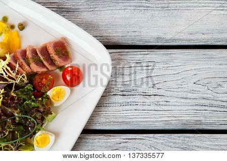 Plate with salad. Salad with tomatoes and meat. Boiled eggs and fried tuna. Organic meal served at bistro.