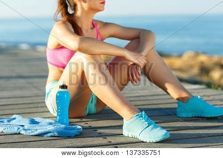 Sunny morning on the beach athletic woman resting after running at the morning training by the sea