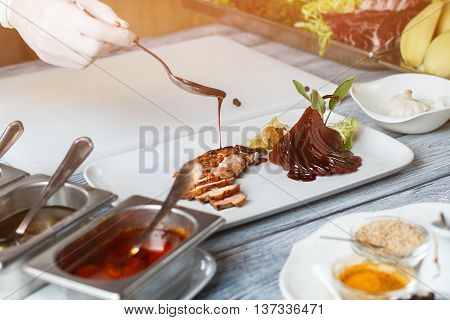 Liquid pouring on cooked meat. Hand holding spoon over plate. Duck steak prepared by chef. Delicious sauce for poultry meat.
