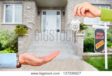 Hand with a key over new house background.