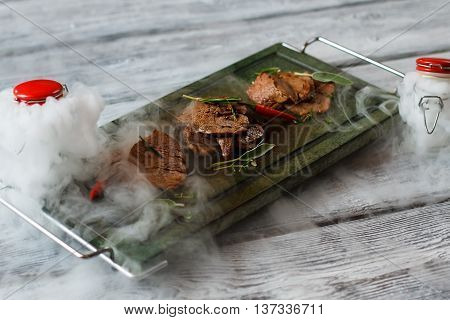 Tray with pieces of meat. Brown meat and green herbs. Veal medallions served at restaurant. Delicacy served with dry ice.
