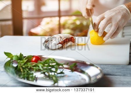 Hand with knife cuts lemon. Raw fish stuffed with tomatoes. Fresh lemon for seafood dish. Chef's new recipe.