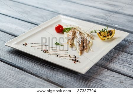 White plate with cooked fish. Cherry tomato and fish fillet. Juicy dorado fish with lemon. Gourmets will enjoy this dish.